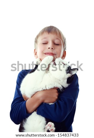 Beautiful happy blond boy embracing a big black and white cat with his eyes closed (isolated on white background)