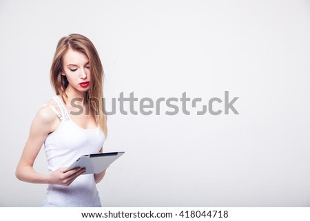 Beautiful happy  blond girl in white  T shirt  and jeans smiling looking at  tablet computer   with copy place on white background on white background