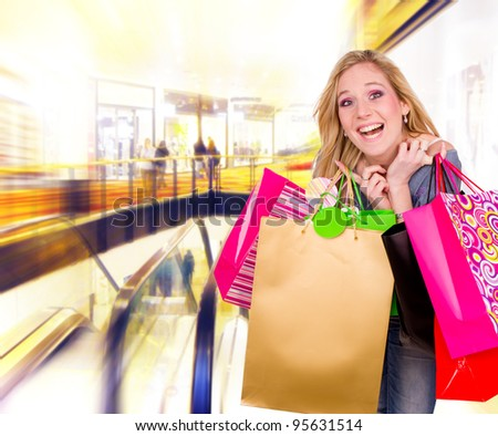 Beautiful happy blond girl with shopping bags - stock photo