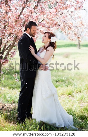 Beautiful happy bride and groom being showered with confetti from cherry blossoms - stock photo