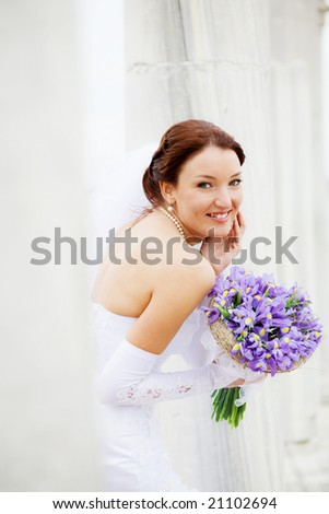 Beautiful happy bride holding wedding bouquet