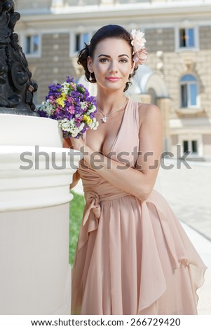 beautiful happy bride in beige dress with plunging neckline smiling standing near city building - stock photo
