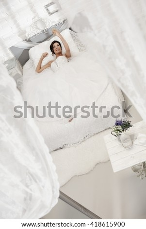 Beautiful happy bride lying on bed in white bedroom, making selfie by mobilephone. - stock photo