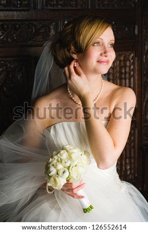 Beautiful happy bride sitting on an old bench, vertical format - stock photo