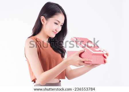 Beautiful happy brunette opening a red gift box. - stock photo