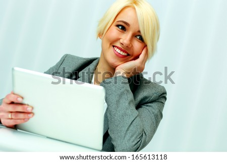 Beautiful happy businesswoman sitting at the table with tablet computer in office