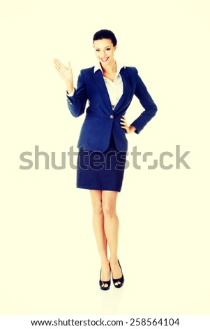 Beautiful happy businesswoman waving her hand. - stock photo