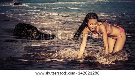 Beautiful happy carefree woman in bikini on beach splashing in ocean water - stock photo