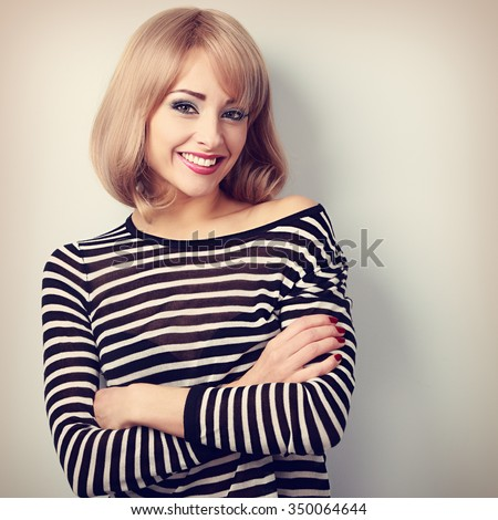 Beautiful happy casual blond woman with folded arms looking with smiling. Toned portrait - stock photo