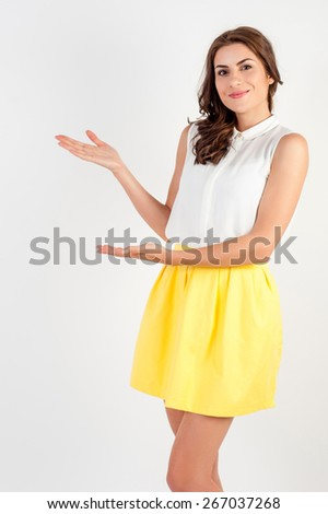 Beautiful happy caucasian model standing playful in yellow dress presenting a copyspace  on white background. - stock photo