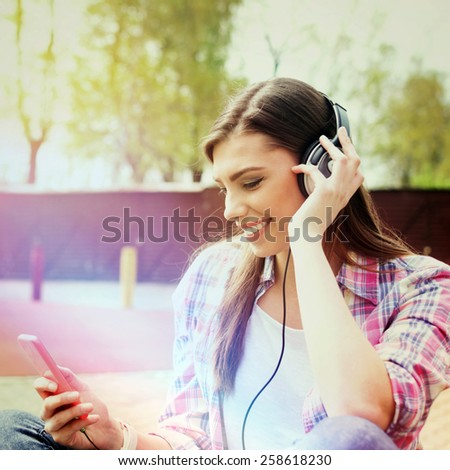 Beautiful happy Caucasian teenage girl with headphones and smartphone in park in spring. Young woman outdoors listening to music on cellphone. Retouched, filter, light leak effect, square format. - stock photo