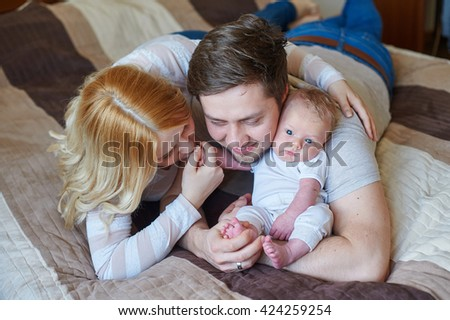 Beautiful happy couple and their baby relaxing in a bed together