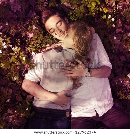 beautiful happy couple embracing, lying on the ground in the spring - stock photo