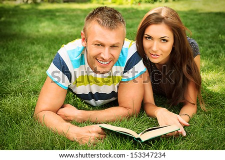 Beautiful happy couple having a rest in the park in sunny summer day.