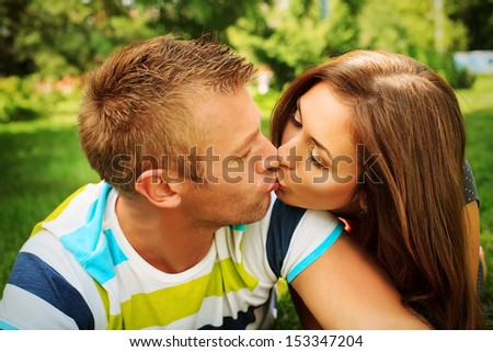 Beautiful happy couple kissing in the park in sunny summer day.