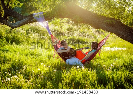 beautiful happy couple relaxing in a hammock. play the guitar. outdoors - stock photo