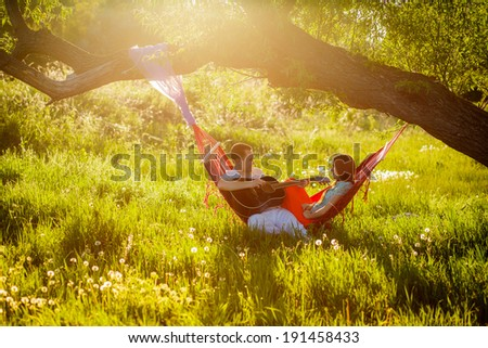 beautiful happy couple relaxing in a hammock. play the guitar. outdoors