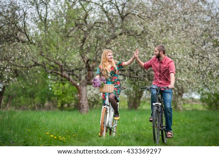 Beautiful happy couple ride bicycles in the blooming spring garden and giving each other a high five. Woman with long blond hair wearing flowered dress and man in a red shirt and jeans. Front view