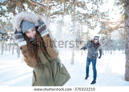 Beautiful happy couple throwing snowballs and having fun in winter park - stock photo