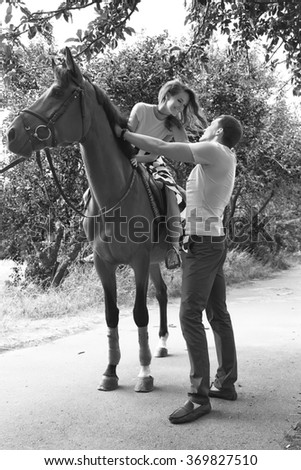 Beautiful happy couple walking in the park, riding a horse, summer, date, passion, happiness, relationships, Valentine's Day, the holiday of lovers, love, dress, husband and wife
