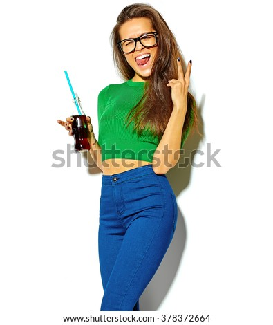 beautiful happy cute brunette woman girl in casual green hipster summer clothes with no makeup isolated on white drinking cola from bottle with straw in glasses,showing her tongue - stock photo