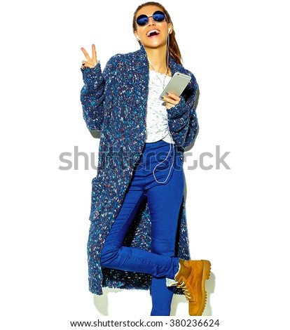 beautiful happy cute smiling brunette woman girl in casual blue hipster summer clothes with no makeup isolated on white in sunglasses listening music in smartphone with headphones showing peace sign
