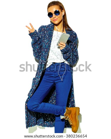 beautiful happy cute smiling brunette woman girl in casual blue hipster summer clothes with no makeup isolated on white in sunglasses listening music in smartphone with headphones showing peace sign - stock photo