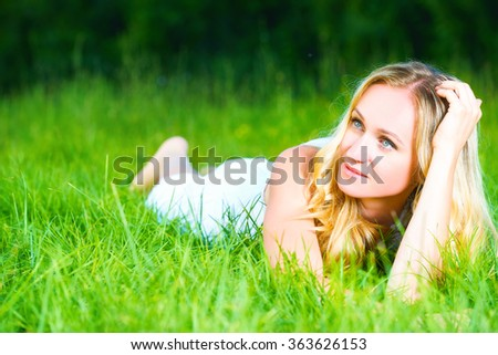 beautiful happy dreamy woman in the summer on nature lying on green grass