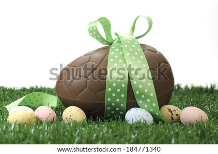 Beautiful Happy Easter large chocolate Easter egg and small candy speckled eggs on grass with white background. - stock photo