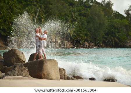 Beautiful happy elderly couple dancing at tropical resort - stock photo