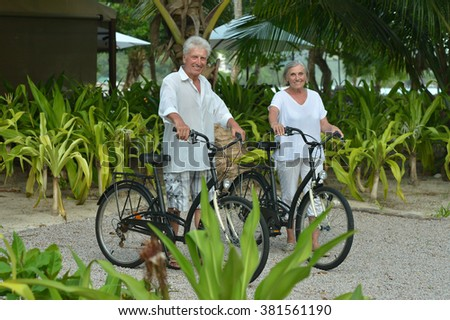 Beautiful happy elderly couple rest with bicycles at tropical resort