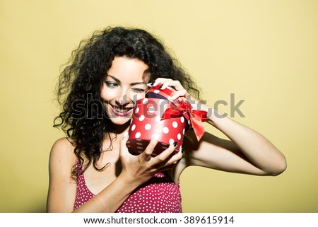 Beautiful happy emotional smiling young adult brunette woman with long curly hair in dress with red present holiday box indoor in studio on yellow background, horizontal picture