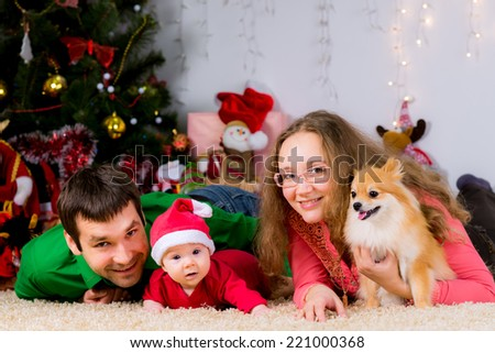 Beautiful happy family and the dog spending Christmas time at home near the Christmas tree. New year concept - stock photo