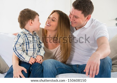 Beautiful happy family having fun at home - parents playing with their son on sofa - stock photo