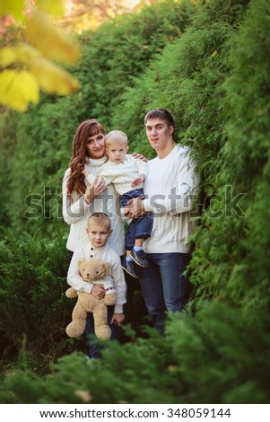 beautiful happy family in sweaters with his two sons in the forest, autumn, summer - stock photo