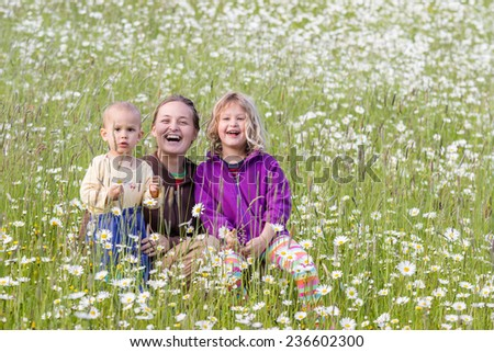 Beautiful happy family on flowering meadow in summer - stock photo