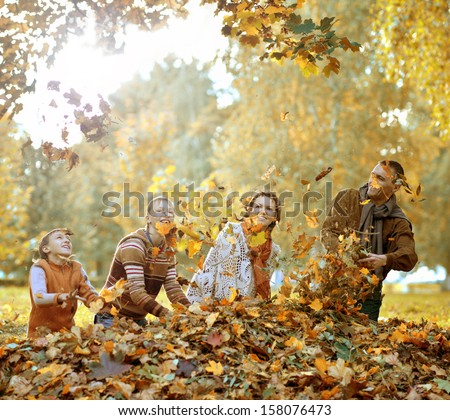 beautiful happy family relaxing in the the park during autumn