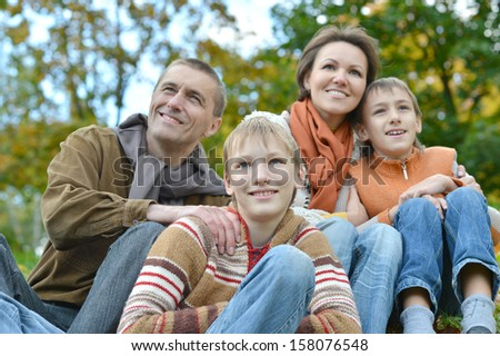 beautiful happy family relaxing on the grass in the park in autumn