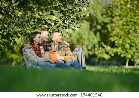 Beautiful happy family relaxing on the grass in the park in autumn - stock photo