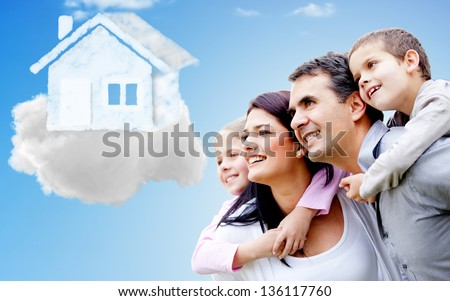 Beautiful happy family thinking of their dream house - stock photo