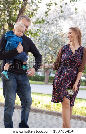 beautiful happy family walks in the flowering trees