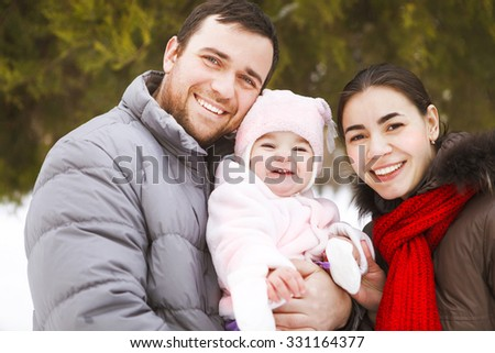 Beautiful happy family wearing warm clothes in winter park