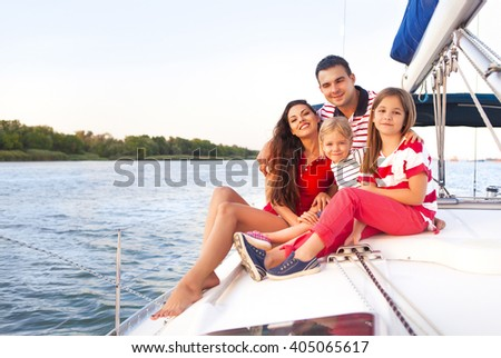 Beautiful happy family with two daughters having great time at the yacht at summertime. Travel and vacation concept
