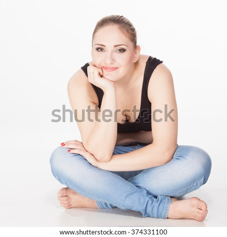 Beautiful happy fat girl sitting cross-legged. dreaminess. Jeans and T-shirt - stock photo