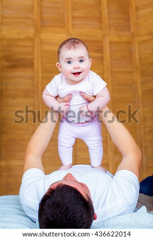 Beautiful happy father with adorable daughter plays on the bed, on the background of  cozy bedroom. Happy childhood. Background, macro, closeup - stock photo