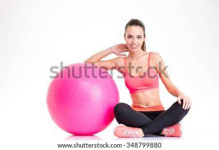 Beautiful happy fitness girl in tracksuit sitting and posing with pink fitball isolated over white background - stock photo