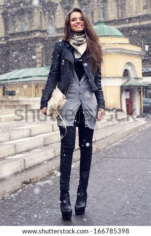 Beautiful happy girl at city street in the snow - stock photo