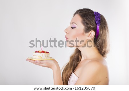 Beautiful happy girl blow out the candle on a birthday cake - stock photo