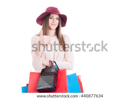 Beautiful happy girl doing shopping and showing like gesture while holding gift bags isolated on white with copyspace - stock photo