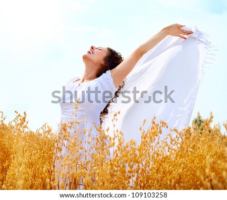 Beautiful Happy Girl Having Fun on the Wheat Field. Healthy Young Woman Outdoors. Oats. Countryside. - stock photo